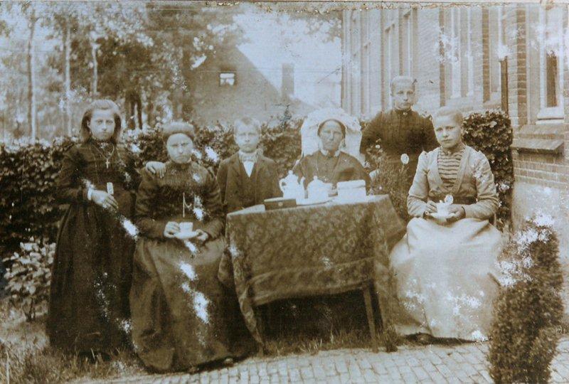 ca1920 Onbekende familie aan de thee, voor groot gebouw met toogramen